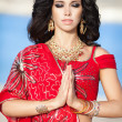 Beautiful Indian Woman in Traditional red dress and golden jewelry outdoors — Stock Photo