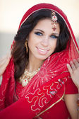 Beautiful Indian Woman in Traditional red dress and golden jewelry outdoors — Zdjęcie stockowe