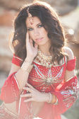 Beautiful Indian Woman in Traditional red dress and golden jewelry outdoors — Foto Stock