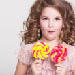 Funny child with candy lollipop, happy little girl eating big sugar lollipop, kid eat sweets. surprised child with candy. — Stock Photo #37930505