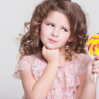 Funny child with candy lollipop, happy little girl eating big sugar lollipop, kid eat sweets. surprised child with candy. — Stock Photo #37930525