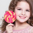 Funny child with candy lollipop, happy little girl eating big sugar lollipop, kid eat sweets. surprised child with candy. — Stock Photo #37930555