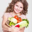 Happy little girl with basket of vegetables, — Stock Photo