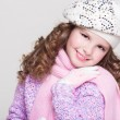 Lovely little girl in winter knitted hat pink scarf gloves and colorful cozy sweater. — Stock Photo #37930701