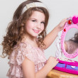 Cute little girl with toy mirror and lipstick. — Stock Photo #37930795