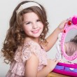 Cute little girl with toy mirror and lipstick. — Stock Photo #37930799