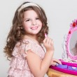 Cute little girl with toy mirror and lipstick. — Stock Photo #37930803