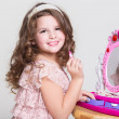 Cute little girl with toy mirror and lipstick. — Stock Photo