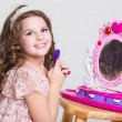 Cute little girl with toy mirror and lipstick. — Stock Photo #37930805