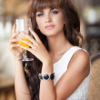 Pretty Young woman in cafe drinking juice outdoors. — Stock Photo