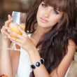 Pretty Young woman in cafe drinking juice outdoors. — Stock Photo #37931417