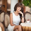 Beautiful Woman at cafe eating cheesecake dessert and drinking juice. — Stock Photo