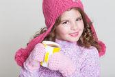 Beautiful child in winter hat drinking hot chocolate — Stock Photo