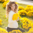 Happy pregnant woman outdoors with spring flowers in green park — Stock Photo #38380763