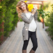 Happy pregnant woman outdoors with spring flowers in green park — Stock Photo