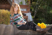 Beautiful pregnant woman relaxing outdoors in park — Stock Photo