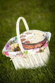 Cookies in picnic basket on green lawn — Stock Photo