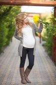 Açık havada bahar çiçekleri yeşil park ile mutlu bir hamile kadın — Stok fotoğraf