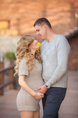 Young pregnant woman with husband walking outdoor and hugs tummy — Stock Photo