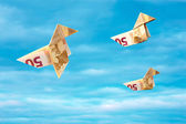 Bank note paper birds flying away on blue sky — Stock Photo