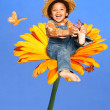 Child sitting on a huge flower playing with butterflies laughing — Stock Photo #26441971