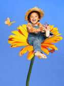 Child sitting on a huge flower playing with butterflies laughing — Stock Photo