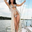 Young woman in swimsuit standing on yacht at sunny day — Stock Photo #26238017