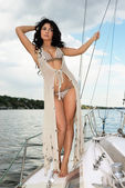 Young woman in swimsuit standing on yacht at sunny day — Stock Photo