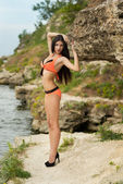 молодая девушка в купальнике на скалах у моря — Стоковое фото