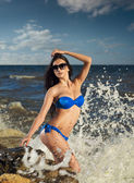 Young girl in a swimsuit on the rocks near the sea — Stock Photo