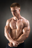 Healthy muscular young man posing in studio — Stock Photo