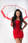 Young girl posing in studio with umbrella — Stock Photo