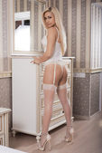 Young blond girl in erotic lingerie posing in the interior — Stock Photo