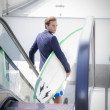 Businessman with surfboard on escalators outside office — Stock Photo