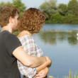 Young couple at river watching swans — Stock Photo