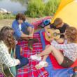 Group of friends camping at river and playing guitars — Stock Photo #32467797