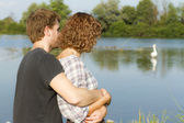 Young couple at river watching swans — Stockfoto