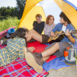Group of friends camping at river and playing guitars — Stock Photo #32942463