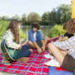 Group of friends camping at river and playing guitars — Stock Photo