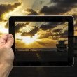 Hand holding a tablet on beach sunset — Stock Photo
