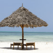Isolated Wooden parasol and beach chairs in Zanzibar — Stock Photo
