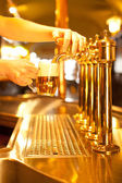 Beer under spigot — Stock Photo