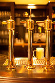 Glass of the beer and gold spigot — Stock Photo