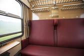 Train compartment with red seats and a view out the window — Stock Photo