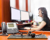 Call center with young woman background headpones detail low dept of filed — Stock Photo