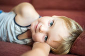 Portrait of young boy lying on sofa at home — Stock Photo