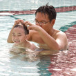 Boy having fun in pool with man - Stock Photo