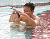 Boy having fun in pool with man — Stock Photo