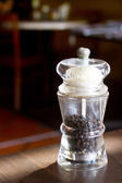 Black pepper in container on a table — Stock Photo