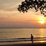 Man running along beach during sunset — Stock Photo #24595689
